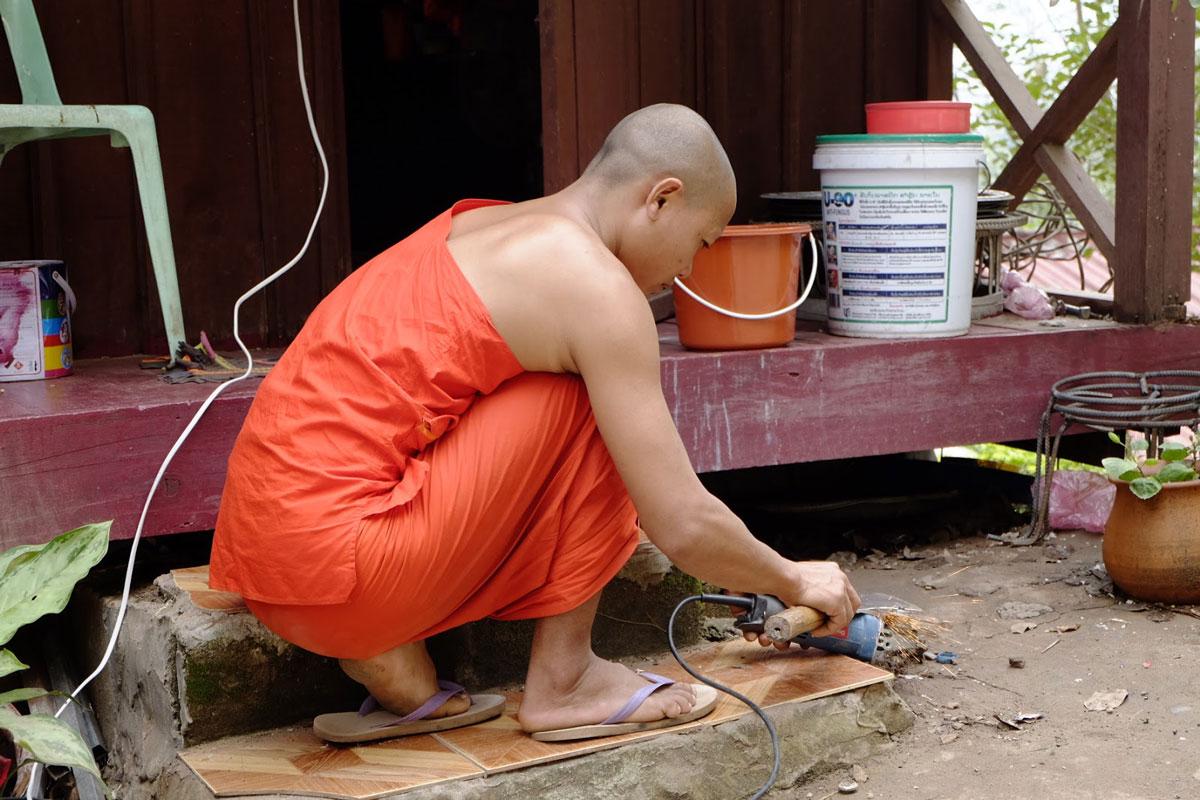 Monaco buddhista al lavoro in un tempio a Luang Prabang