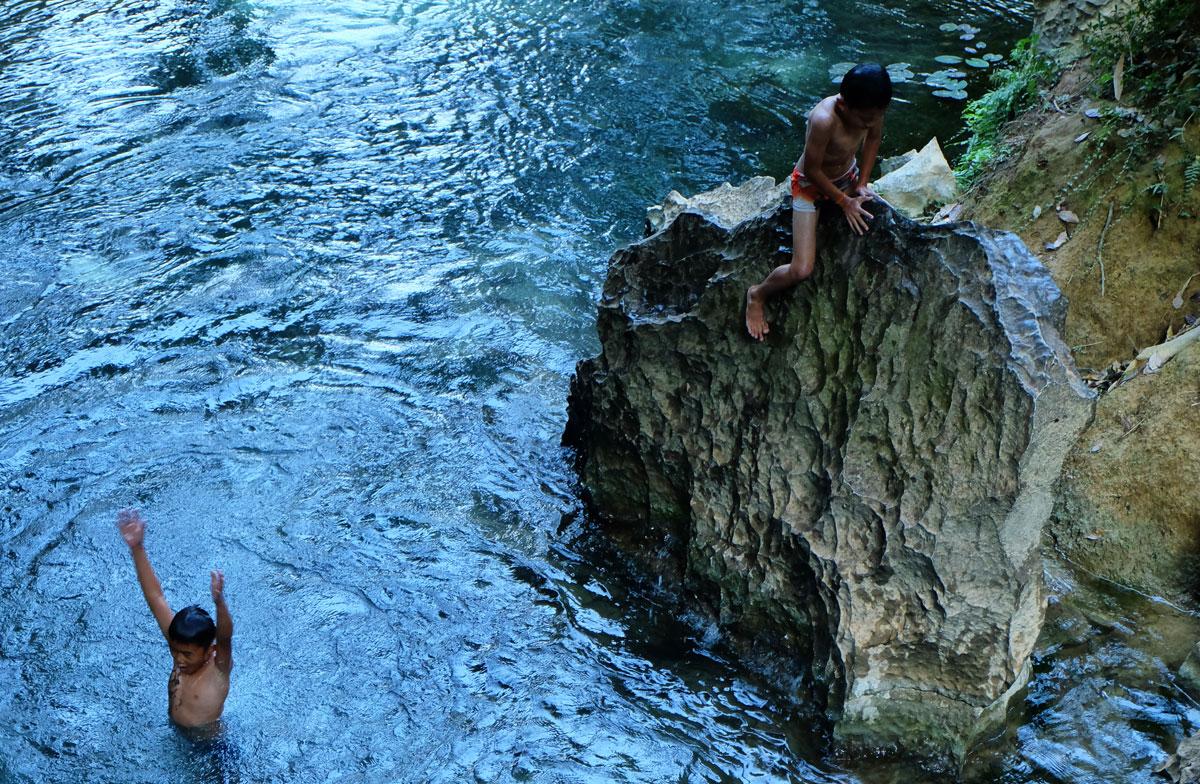 Bambini tuffo nella laguna Laos
