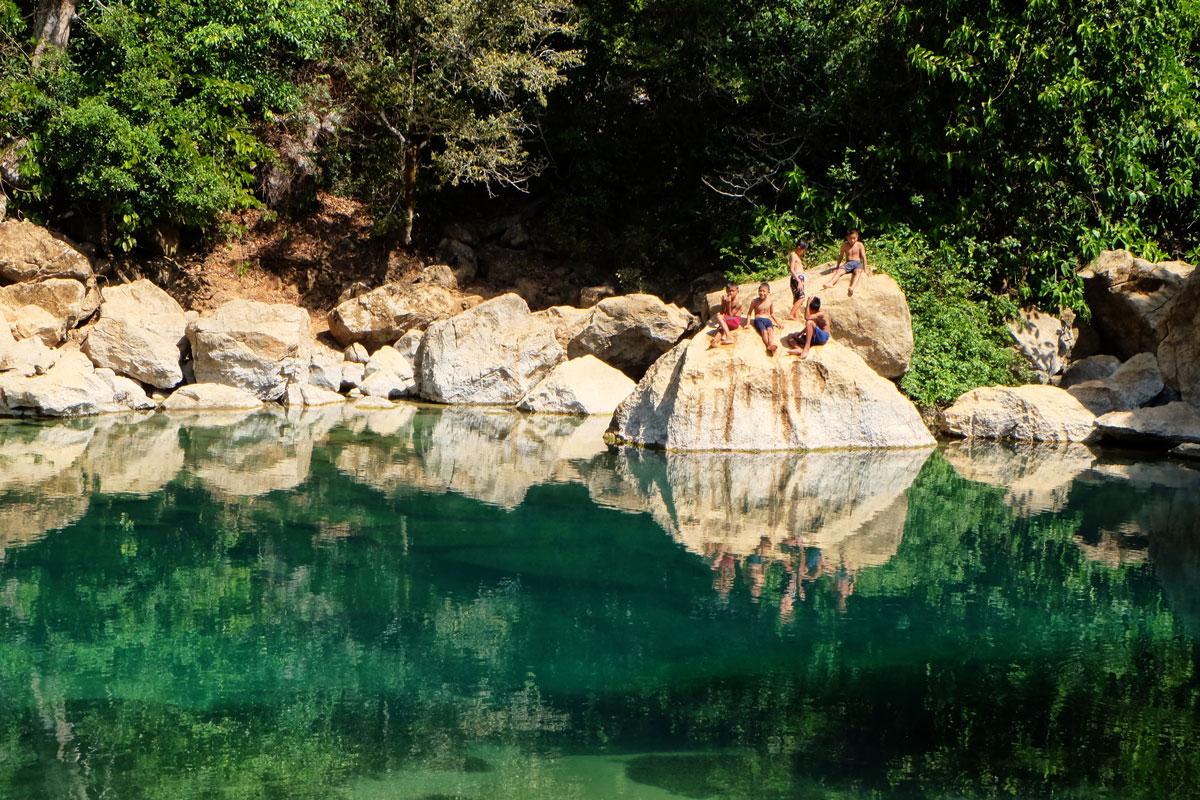 Laos zaino in spalla e si incontrano bambini che fanno il bagno in una laguan