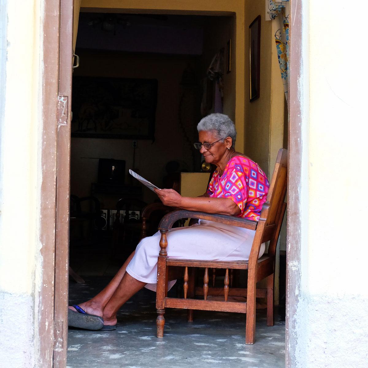 Anziana donna che legge a Cuba sull'uscio di casa.