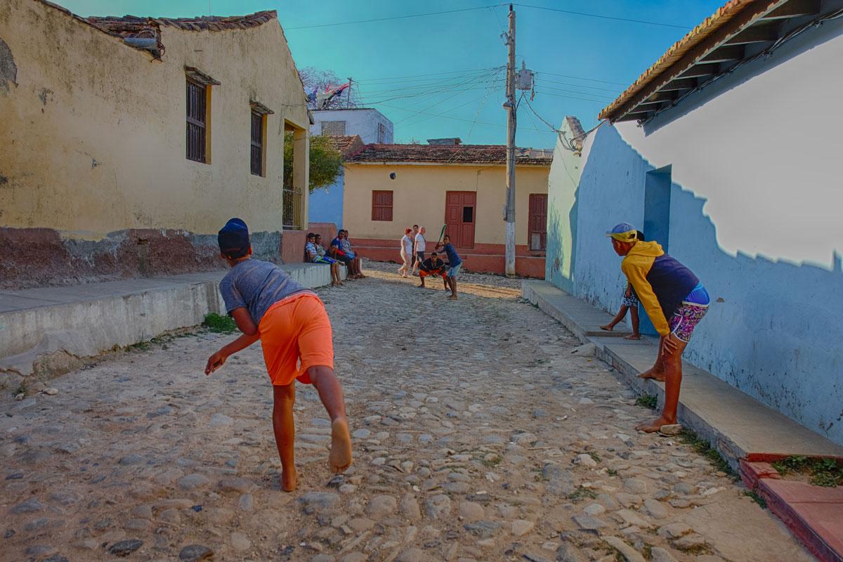 Bambini per strada che giocano a baseball a Cuba