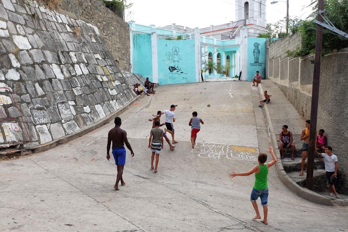 I racconti di viaggio in una foto in cui dei bambini giocano a calcio per strada a Santiago de Cuba