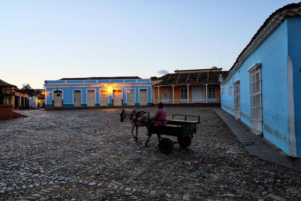 Centro storico deserto di Trinidad con uomo su un carretto trainato da cavallo.