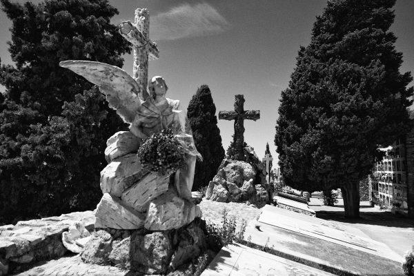 Statua in marmo di angelo con croce nel cimitero di Montjuic