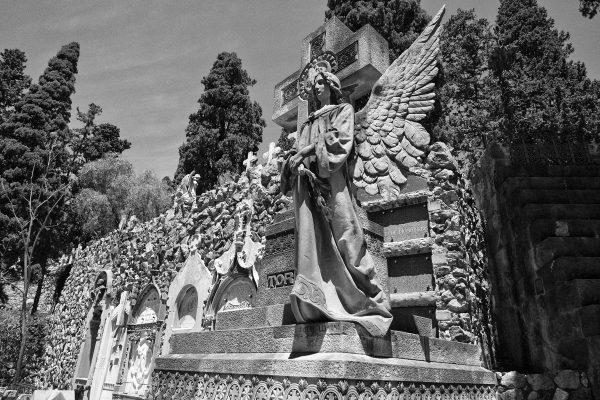 Statua in marmo di angelo e croce nel cimitiero di Montjuic
