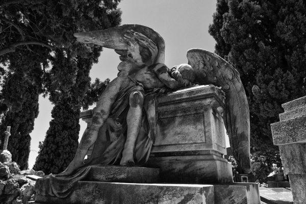 Statua di marmo di angelo che piange su una tomba nel cimitero di Montjuic